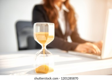 Asian businesswoman posing on the table with hourglass at office background