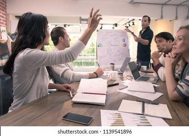 Asian businesswoman raising hand and asking questions and discussing to businessman during team business meeting in modern office, diverse group of colleagues people looking to her with interesting.