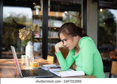 Asian businesswoman serious about the work done until the headache and she is work from home for social distance and self responsibility concept