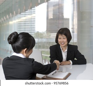 Asian businesswoman shaking hands with colleague