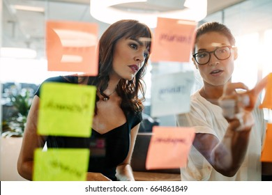 Asian businesswoman showing her coworker an idea posted on a sticky note wall. Creative professionals brainstorming on new business ideas.