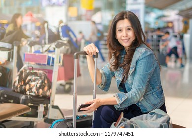 Asian businesswoman sitting at the airport, waiting for the flight. Thoughtful woman sitting on bench at airport waiting area.