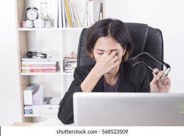 asian businesswoman sitting at the table computer in office with massaging his nose and keeping eyes.