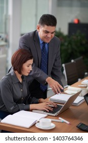 Asian businesswoman sitting at the table and typing on laptop computer while her colleague pointing at monitor and talking to her in board room