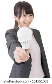 Asian businesswoman is smiling while giving you a light bulb. Portrait isolated on the white background.
