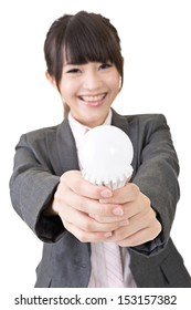 Asian businesswoman is smiling while holding with both hands a light bulb. Portrait isolated on the white background.