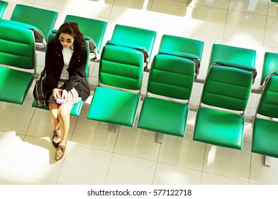 Asian businesswoman in sunglasses sitting at airport waiting area holding her passport waiting for boarding an airplane