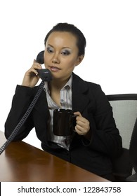 Asian businesswoman talking through her telephone while having coffee