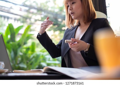 An Asian businesswoman is teleconferencing with her client using her laptop.  She 's trying to explain something to her customer and you can see her hand is moving.
