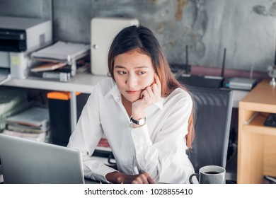 Asian businesswoman thinking looking out of window in front of laptop computer screen for planning work in office,Office lifestyle concept.