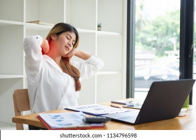 Asian businesswoman touching massaging stiff neck to relieve pain in muscles working in incorrect posture.