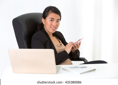 Asian businesswoman typing on her telephone sitting at desk in office
