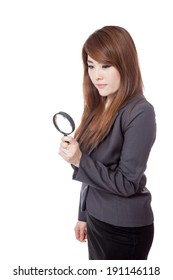 Asian businesswoman use magnifying glass looking down isolated on white background