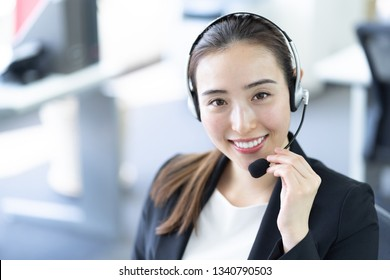 asian businesswoman using headset in office