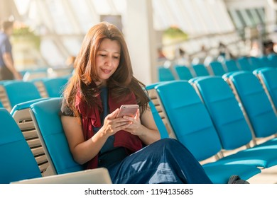 Asian businesswoman using mobile phone with feeling happy and smiley face, check flight at the international airport to travel on weekends at gate waiting in airport terminal.