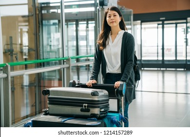 asian businesswoman walking with hand luggage in airport going to boarding gate. young woman happy sucessfully finished the trip in japan and going to leave back to home.
