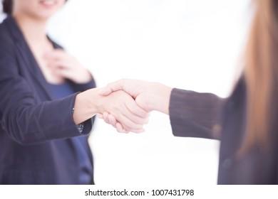 Asian Businesswomen handshake, dark blue and blurred background.
