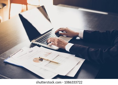 Asian businesswomen holding a pen and analysis documents on office table with laptop computer and graph financial diagram working in the background