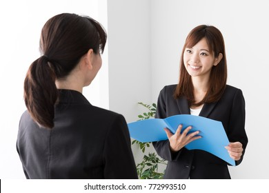 asian businesswomen talking in office