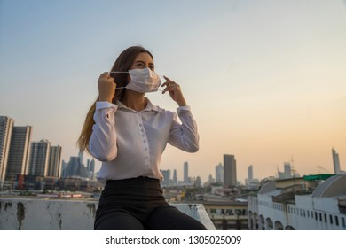 Asian Businesswomen wearing masks to prevent air pollution at the capital of Bangkok .Bangkok Thailand has pollution problems.