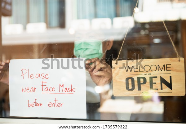 Asian cafe or restaurant shop owner woman attaching request customer to wear face mask before enter cafe sign board at entrance door for prevent corona virus infection after lock down from pandemic.