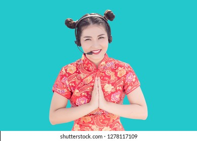 Asian call centre with cheongsam Qipao Chinese Traditional dress in warm welcome service on blue isolated background in pop art colour theme for China New year festival. (include clipping