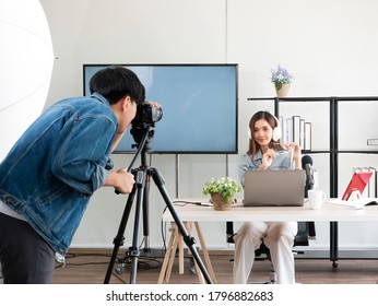 Asian camera man and pretty influencer recording live video about game product review with microphone and share screen from laptop device for broadcast on channel or social media in home studio setup
