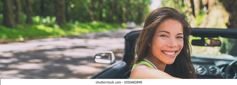 Asian car driver woman smiling happy relaxing in convertible car on summer road trip vacation. Travel destination driving through Hawaii, banner panorama.