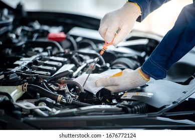 Asian car mechanic in an auto repair shop is checking the engine. For customers who use cars for repair services, the mechanic will work in the garage.