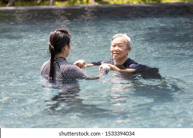 Asian caregiver woman is supporting,care the elderly people walking,exercising in the water,happy and healthy senior mother in swimming pool with daughter,health care,physical therapy concept