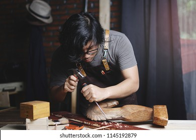 Asian Carpenter Working in Woodworking Workshop. Carving Wooden Horse Sculpture