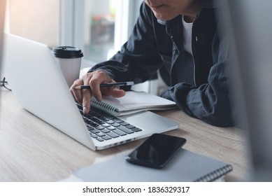 Asian casual business man working on laptop computer, browsing internet and taking notes on paper notebook at home office. Student concentrate learning online and lecturing on notepad, close up