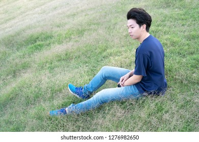 Asian CASUAL man sitting on a grassland view background. Portrait of young KOREAN against grassland  background. - relaxing concept.
