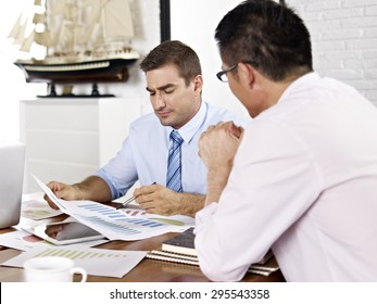 asian and caucasian business executives reviewing and discussing business performance in office of a multinational company.