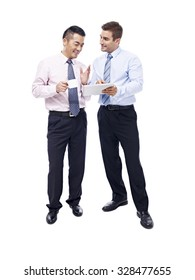 asian and caucasian business men having a discussion with coffee cup and tablet computer in hands, isolated on white background.