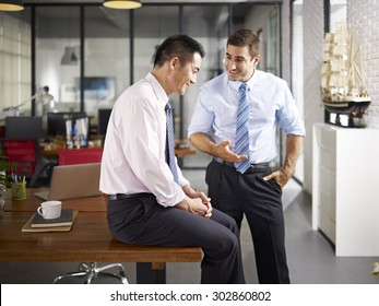 asian and caucasian businessmen enjoying a pleasant conversation in office of a multinational company, focus on the man sitting.