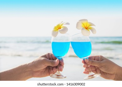 Asian Ccouple holding cocktail glass decoration with plumeria flower with wave sea beach background - happy relax celebration vacation in sea nature concept