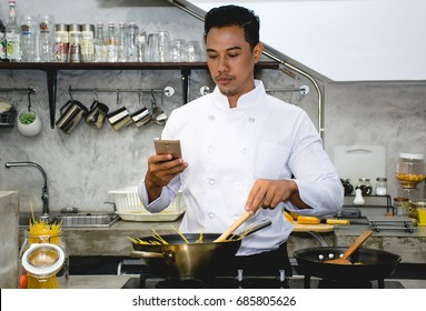 Asian chef is cooking food by following the online video instruction at the kitchen of a restaurant