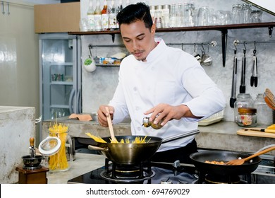 Asian chef is cooking food by using wooden ladle at the kitchen of a restaurant
