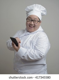 Asian chef with mobile device in her hand on plain background