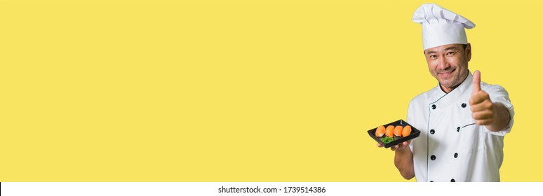 Asian chef showing plate with sushi and OK. Focus on sushi. Banner edition. Isolated on yellow background.