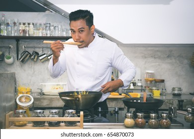 Asian chef is tasting food by using wooden ladle at the kitchen of a restaurant