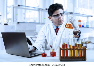 Asian chemist working in laboratory and doing research