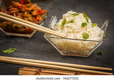 Asian chicken with vegetables and rice in glass plate