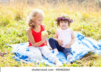 Asian child along with his caucasian girlfriend on a picnic in the mountains on a Sunny day