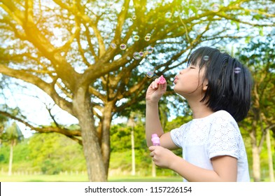 Asian child blowing bubbles in the park