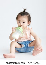 Asian child with bottle, shot in studio white background