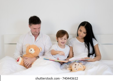 Asian child boy reading book together on bed in bedroom with father and mother. Happy family concept.