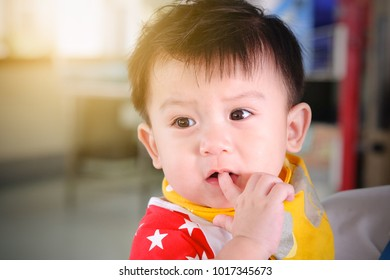 Asian child boys are looking and sucking finger in mouth