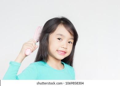asian child brush her black hair with pink hair brush